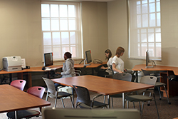 The HIL seminar room with computers arranged around the perimeter, tables in the middle, and an instructor workstation.
